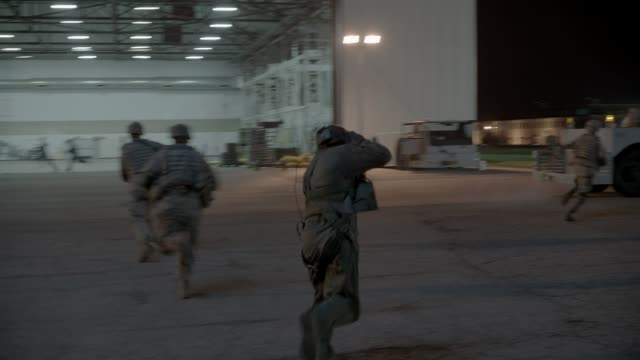 medium angle of soldiers and military personnel running in panic on military base. airplane hangar. could be under attack. trucks and military vehicles. emergency. - airplane hangar stock videos & royalty-free footage