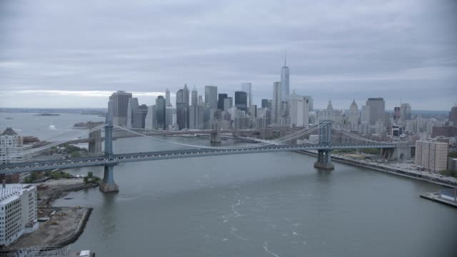 aerial of manhattan and brooklyn bridges over east river. downtown manhattan new york city skyline with skyscrapers and high rise office or apartment buildings. cloudy. - マンハッタン橋点の映像素材/bロール