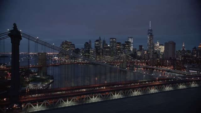 aerial of manhattan and brooklyn bridges over east river. downtown manhattan new york city skyline with skyscrapers and high rise office or apartment buildings. - マンハッタン橋点の映像素材/bロール