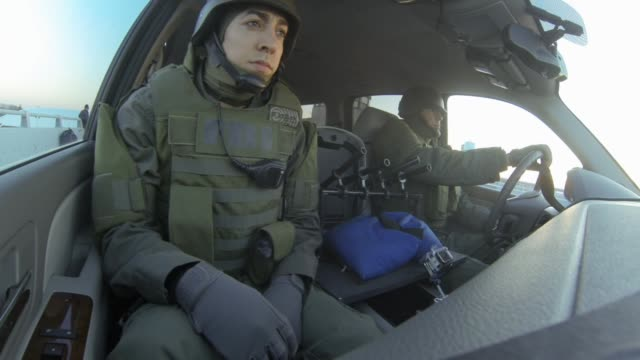 medium angle of two fbi agents in riot gear in front seat of suv. shootout occurs killing agents. could be attack. stunts. - sports utility vehicle stock-videos und b-roll-filmmaterial