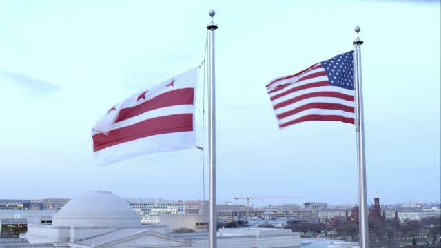 medium angle of american flag. domed building partially visible in bg. washington dc flag raised. - washington dc stock videos & royalty-free footage
