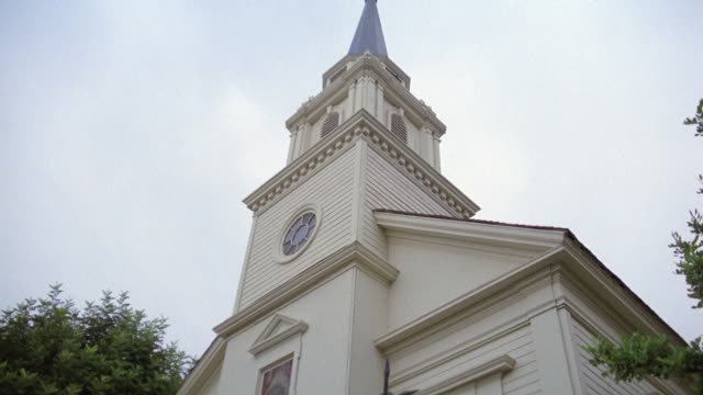 pan up on white wooden church to steeple. could be in small town. - anno 1987 video stock e b–roll