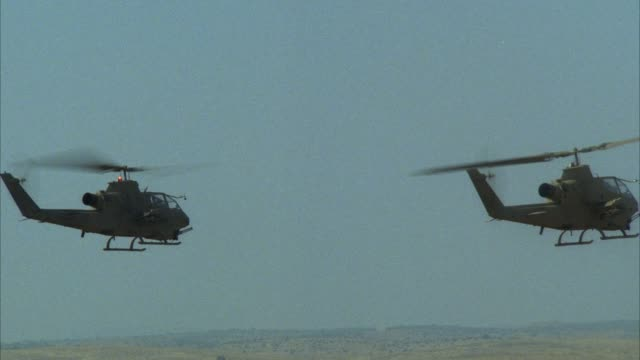 tracking shot of two camouflage military helicopters hovering in air. - air vehicle stock videos & royalty-free footage