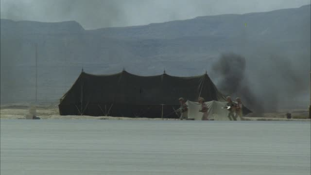 tracking shot of a military camp with pitched tents and black smoke. - army stock videos & royalty-free footage