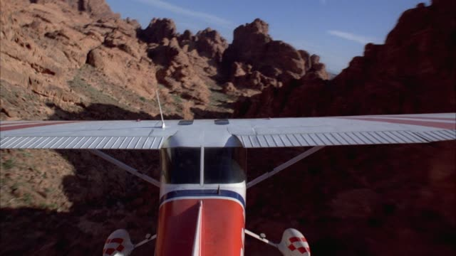 aerial of a small red and white passenger airplane flying through a desert area - airplane tail stock videos and b-roll footage