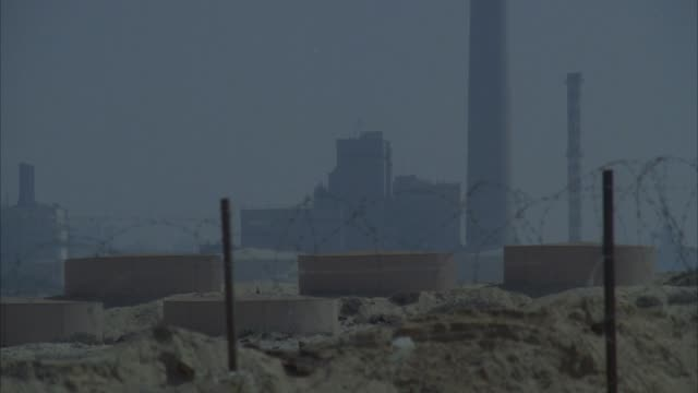 medium angle of military base or industrial area with barb wire fence and sandy area in foreground. - industrial district stock videos & royalty-free footage