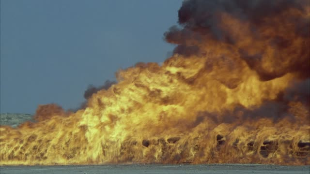 medium angle of a raging fire with black smoke. - jumping stock videos & royalty-free footage