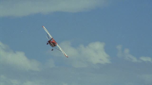 up angle of tail of propeller powered stunt airplane banking right. shot tracks plane. see underside of plane. see red stripes on underside of wings. see clouds in blue sky. middle east. - airplane tail stock videos and b-roll footage