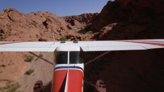 medium angle of propeller driven white, red, and blue stunt  airplane. - airplane tail stock videos and b-roll footage