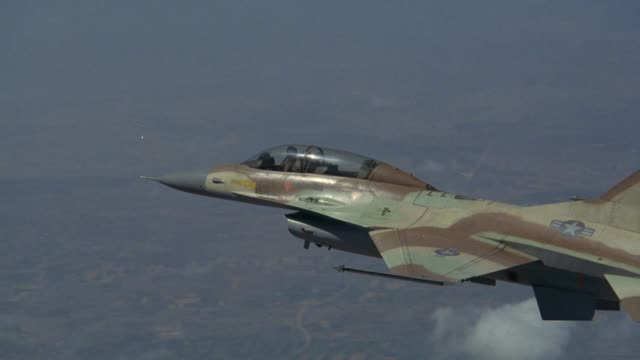 aerial shot of american camouflage jet f-16 fighter plane over land. see shot pull back to show jet body. jet rolls right out of shot. middle east. - general dynamics f 16 falcon stock videos & royalty-free footage