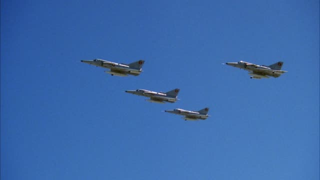 aerial of four saab viggen 37e jet fighter planes flying in formation. shot pans up to top two planes. blue sky in background. middle east. - formationsfliegen stock-videos und b-roll-filmmaterial
