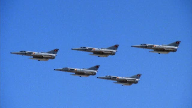 aerial of five saab viggen 37e jet fighter planes flying in formation. bottom right jet banks right and drops out of shot. two forward jets fly up out of shot. two remaining jets bank right down out of shot. blue sky in background. middle east. - formationsfliegen stock-videos und b-roll-filmmaterial
