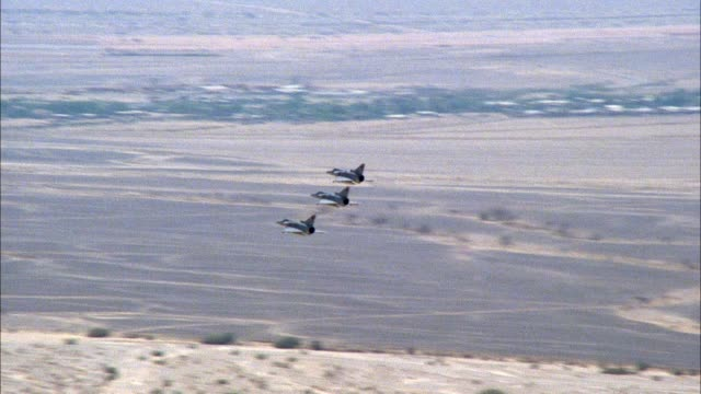 air-to-air aerial tracking shot of five military jet saab viggen 37e fighter planes flying right to left in formation maneuver. see cliffs, desert floor in background. middle east. - krieg stock-videos und b-roll-filmmaterial