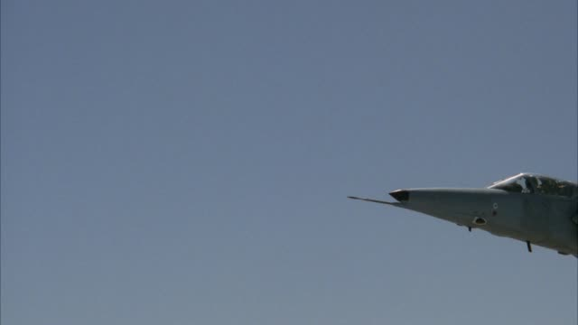 medium angle of saab viggen 37e fighter jet plane flying into shot from right. jet then rolls right and down out of shot. see bottom or underbelly of jet. see missiles or bombs. middle east. - mezzo di trasporto aereo video stock e b–roll