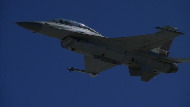 up angle of jet f-16 fighter plane from beneath left wing. see entire jet, underbody, missiles, pilot. blue sky in background. - general dynamics f 16 falcon stock videos & royalty-free footage