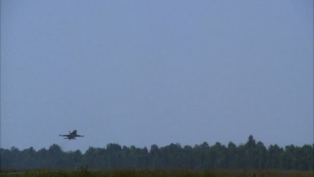 medium angle of f-16 fighter jet plane on runway. see jet in distance. see jet from front right. jet takes off then flies over camera. shot pans up to follow jet. shot then pans down to focus on runway. middle east. - fighter stock videos & royalty-free footage