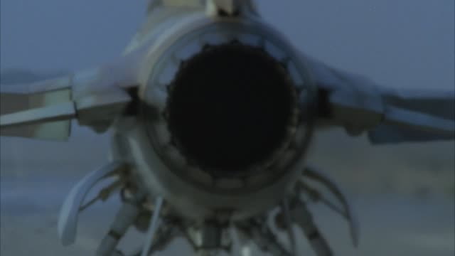 medium angle of f-16 jet fighter taking off. pov behind jet. see jet engine as jet starts to roll forward. then see afterburner or orange glow from exhaust. cut to jet pulling up in sky. middle east. - afterburner stock videos and b-roll footage