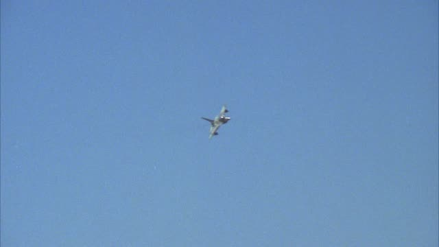 tracking shot of f-16 fighter jet flying right across screen. banks right and turns around out of shot. middle east. - general dynamics f 16 falcon stock videos & royalty-free footage