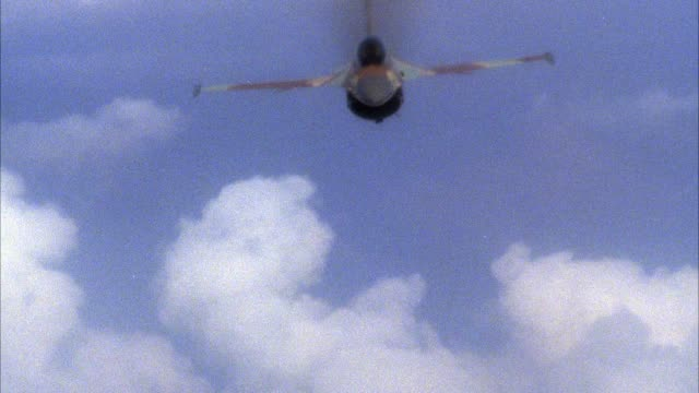 medium angle of camouflage f-16 fighter jet flying toward camera. jet rolls left. see clouds and blue sky in background. - general dynamics f 16 falcon stock videos & royalty-free footage