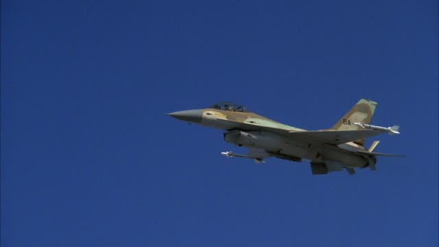 tracking shot of f-16 fighter jet flying in blue sky from beneath left wing. shot zooms in for closer view of cockpit and pilot. shot pans right then left. - general dynamics f 16 falcon stock videos & royalty-free footage