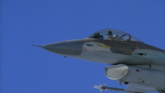 tracking shot of f-16 fighter jet flying in blue sky from beneath and left of cockpit. - general dynamics f 16 falcon stock videos & royalty-free footage