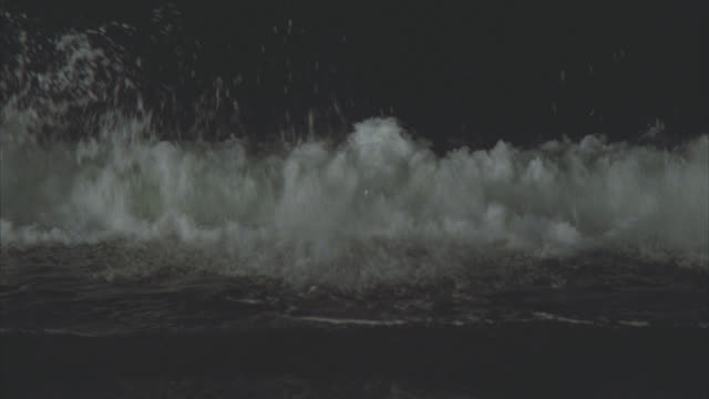 medium angle of ocean waves breaking on beach or shore. full moon in sky. - full moon stock videos & royalty-free footage