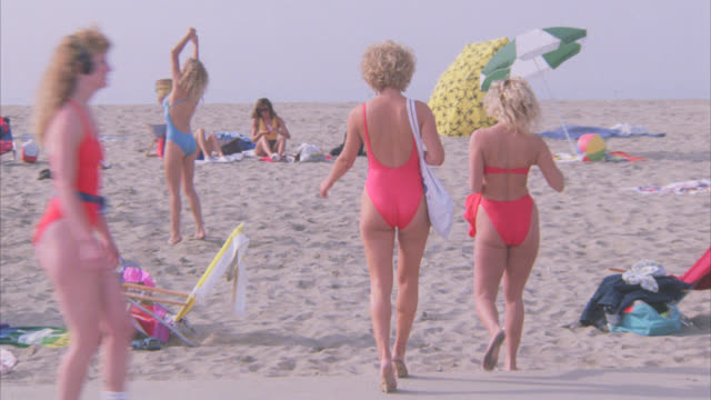 pan up to people on beach. volleyball game. bikini-clad women. pier or boardwalk in bg. sand. roller-skating. - 1986 stock videos and b-roll footage