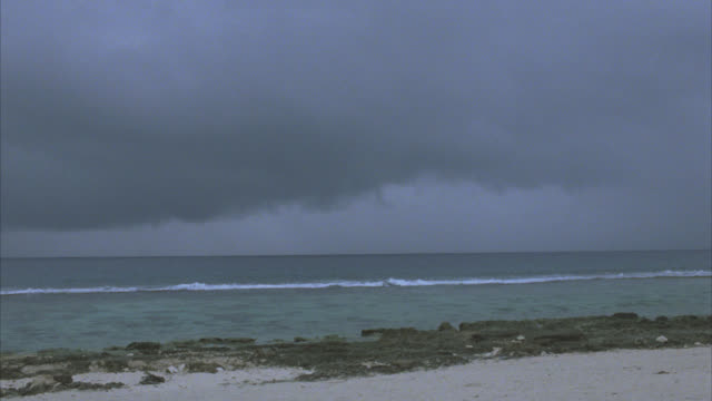 wide angle of ocean and beach. rocky. overcast sky. cloudy. sand on shore. - tahiti stock videos & royalty-free footage