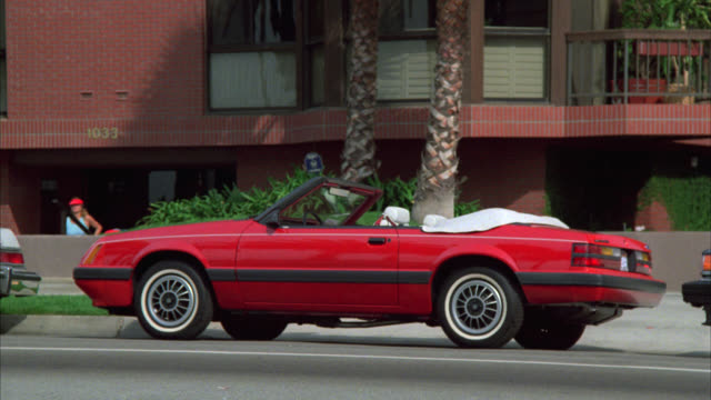pull back from red ford mustang convertible car to show upper class four story brick apartment or complex. palm trees. - mustang convertible stock videos & royalty-free footage