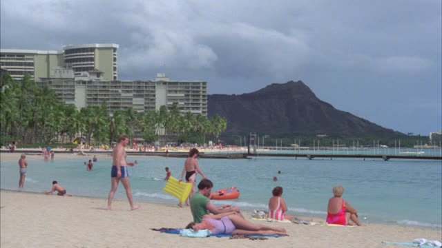 vídeos y material grabado en eventos de stock de zoom in from est ground level shot of waikiki beach with sunbathers hotels on left to diamond head in bg. multiple takes. tropical island. - honolulu