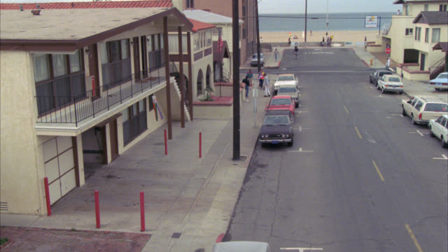 stockvideo's en b-roll-footage met pan down to est street in venice beach. hammer crosses street and enters small one story beach house. - venice california