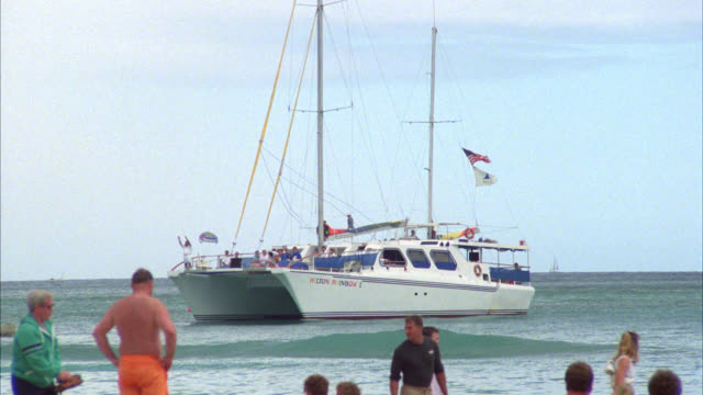 pan right to left of rainbow yacht or boat sailing in ocean near beachfront. people on beach. - anno 1987 video stock e b–roll