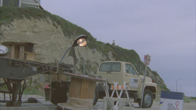 PAN LEFT TO RIGHT AS POLICE CAR CRASHES THROUGH CONSTRUCTION AREA ON BEACH. CLIFF IN BG. OCEAN WAVES ON SAND. STUNT.