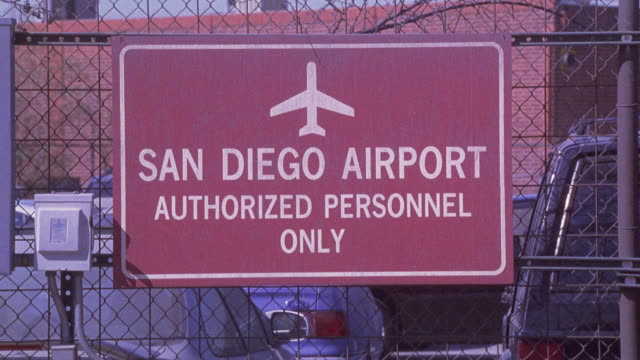 """close angle of red sign reading """"san diego airport authorized personnel only"""" hanging on chain link fence. cars parked in parking lot visible in bg. - hanging sign stock videos and b-roll footage"""