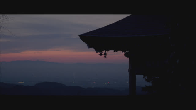 vidéos et rushes de medium angle of a temple or shrine on a mountain overlooking a city or town. see faint lights and mountains in background. sky has a streak of red. could be buddhist. - sanctuaire