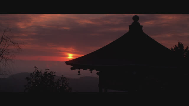vidéos et rushes de medium angle of a temple or shrine with a sunrise in background. temple roof forms a peak. see trees or shrubs in foreground, mountains in background. sky filled with clouds; orange glow of sun shines across horizon. could be buddhist. - sanctuaire