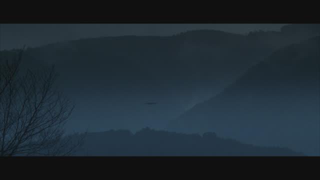 vídeos y material grabado en eventos de stock de medium angle of mountains and tree lines in distance. bare tree in foreground. fog or mist fills shot. - bare tree