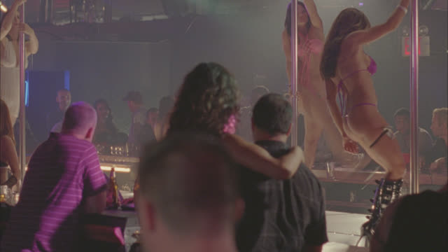vidéos et rushes de medium angle of strip club, bar or night club. men watching women pole dancing. - peep show