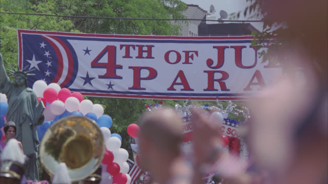 medium angle of fourth of july parade. floats, balloons, cheerleaders, decorations, banners, and flags. crowds of people. - parade stock videos & royalty-free footage