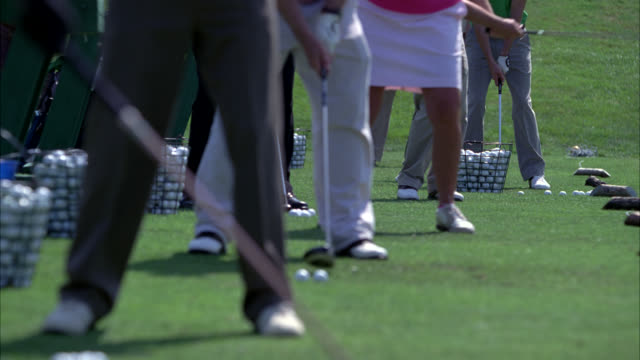 medium angle of men and women hitting golf balls at driving range. legs. golf balls in baskets. - driving range stock videos & royalty-free footage