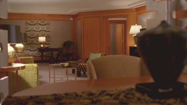 medium angle of middle class hotel room. lamps, sofa, and chairs visible. - 電灯点の映像素材/bロール