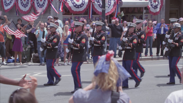 medium angle of fourth of july parade. american flags, banner, crowds, and soldiers. cheering. - fourth of july stock videos & royalty-free footage