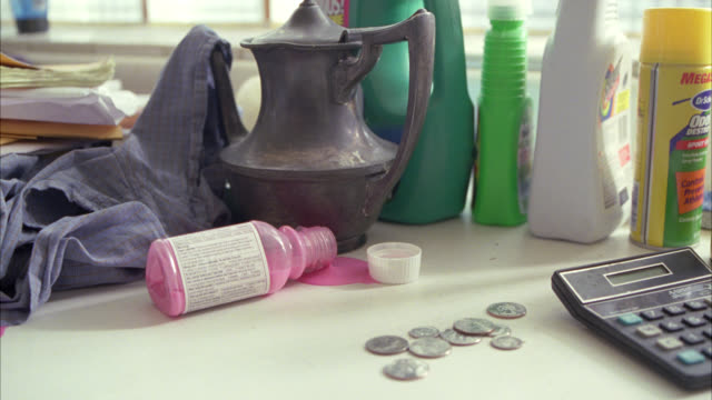 close angle of laundry detergent, shirt, pepto bismol, coins, and calculator sitting on top of counter. could be washing machine. - laundry detergent stock videos and b-roll footage