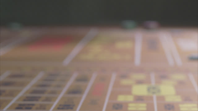 close angle of hands throwing dice on craps table. stickman returns dice with wooden stick. betting chips. gambling games. series. - craps stock videos & royalty-free footage