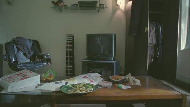stockvideo's en b-roll-footage met medium angle of living room. could be studio apartment. clothes strewn on chair. papers clutter coffee table. messy. - messy