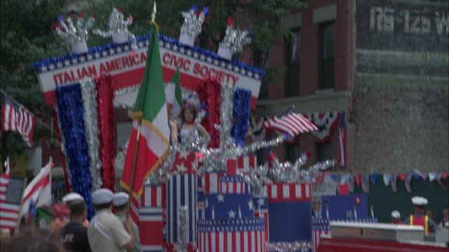 medium angle of fourth of july parade or celebration. people waving american flags. float with sign reading italian american civic society. manhattan ave, greenpoint, brooklyn. - greenpoint brooklyn stock videos & royalty-free footage