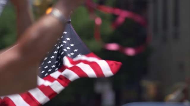 medium angle of people celebrating at fourth of july parade. american flags and decorations visible. crowds. cheerleaders, baton twirlers, marching band, soldiers, and people in convertible cars. - fourth of july stock videos & royalty-free footage