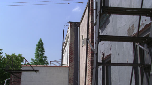medium angle of fire escape ladders on rooftop of lower class multi-story brick apartment buildings. - 非常階段点の映像素材/bロール