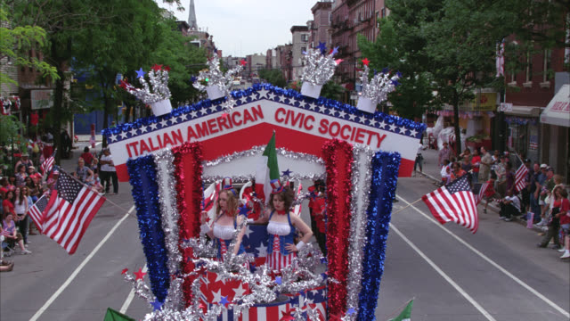 pan down from float with sign for italian american civic society in fourth of july parade on city street. crowd of people in bg waving american flags. manhattan ave, greenpoint, brooklyn. - greenpoint brooklyn stock videos & royalty-free footage