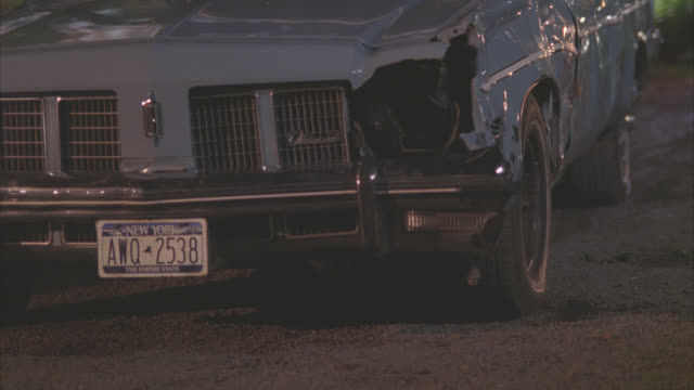 close angle of radiator grille on 1975 oldsmobile delta 88 car. license plate. headlight is missing. car is dented. - number plate stock videos & royalty-free footage